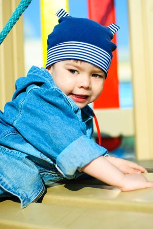 cute three year old boy playing outdoor at the Childrens playground photo