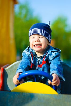 game drive: happy three year old boy driving a toy car outdoor in the park Stock Photo