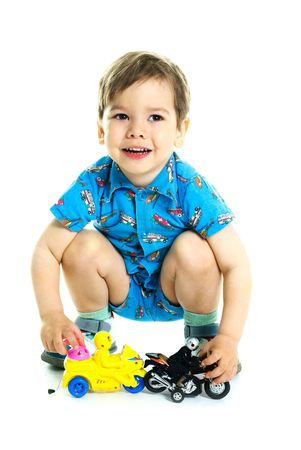 portrait of a cute happy three year old boy playing with toy motorcycles Stock Photo - 4894448