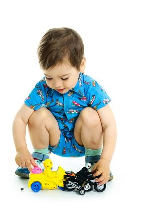 portrait of a cute happy three year old boy playing with toy motorcycles Stock Photo - 4894446
