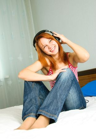 pretty girl sitting on the bed at home and listening to the music Stock Photo - 4904109