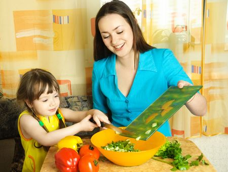 young mother and her little daughter cooking together in the kitchen photo