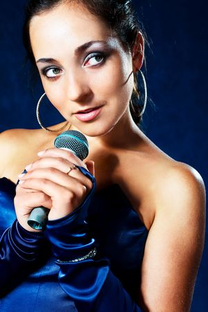 portrait of sexy young beautiful singer with a microphone photo