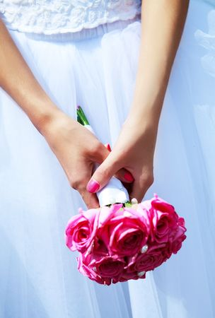 getting a bride: wedding bouquet in the hand of a young bride