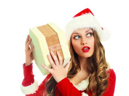 sexy young woman dressed as Santa shaking a present a trying to guess what is inside of it Stock Photo - 5721365