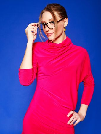 portrait of  a beautiful young blond woman wearing glasses against blue background Stock Photo - 5721435