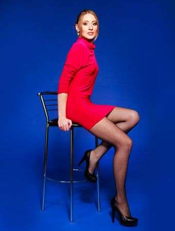 studio portrait of a beautiful young blond woman sitting on the chair Stock Photo - 5721398