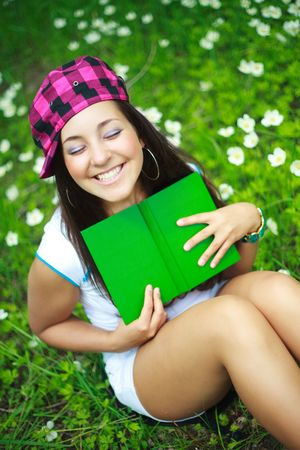 pretty brunette girl reading a book in the park in summertime photo