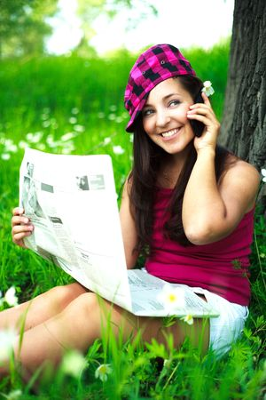 pretty girl talking on the cellphone and reading a newspaper in the park photo