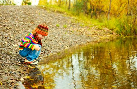 warm water: cute little baoy playing near the lake in the autumn park