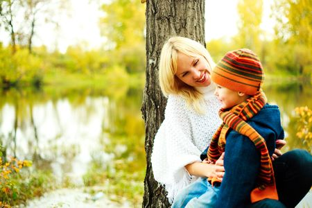 happy young beautiful mother with her little son in the park (focus on the woman) photo