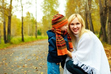 happy young beautiful mother  having a walk in the park with her little son  photo
