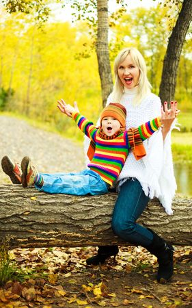 happy young beautiful mother with her little son in the park (focus on the boy) photo