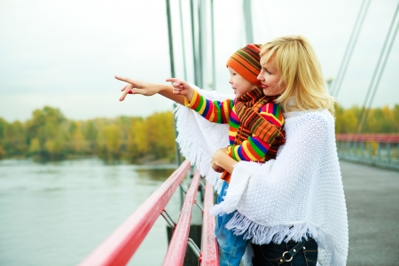 young mother with her little son outdoor on the bridge photo