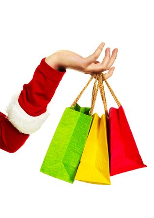 close up of the hand of a woman dressed as Santa holding three shopping bags photo