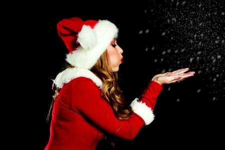 sexy young woman dressed as Santa blowing on the snow photo