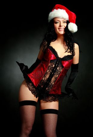sexy young brunette woman wearing a corset and a Santas hat photo
