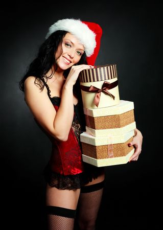 sexy young brunette woman wearing a corset and a Santas hat with Christmas presents photo