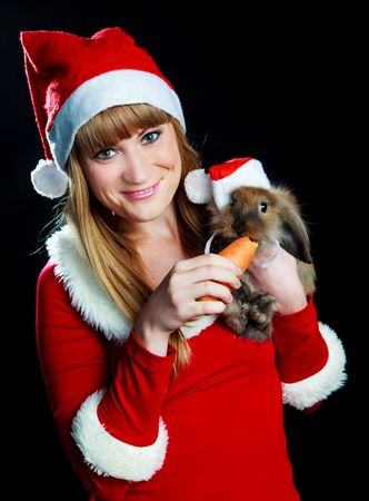 pretty blond woman dressed as Santa with a rabbit wearing a Santa's hat in her hands Stock Photo - 5792543