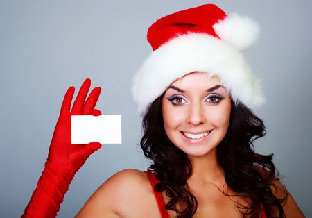 beautiful young brunette woman wearing a Santas hat holding a business card photo