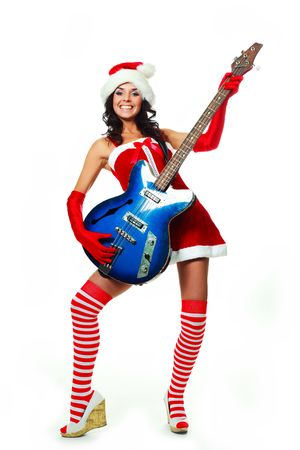 beautiful young brunette woman wearing a Santas hat and playing a guitar photo