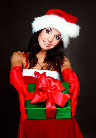 beautiful brunette girl dressed as Santa giving us a present Stock Photo - 5811647