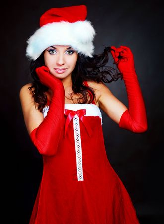 studio portrait of a sexy young brunette woman dressed as Santa against dark background photo