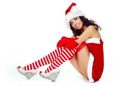 beautiful dreamy brunette girl dressed as Santa sitting on the floor photo