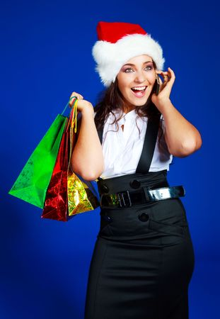 beautiful brunette girl wearing a Santas hat with a lot of shopping bags talking on the cellphone photo