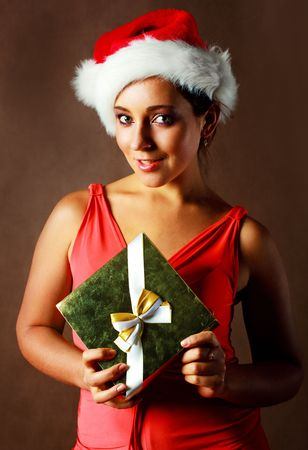 beautiful young brunette woman wearing a Santas hat with a Christmas present photo