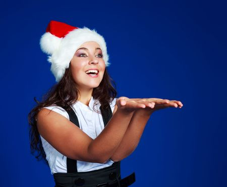young brunette businesswoman wearing a Santas hat with her hands up, place your product here photo