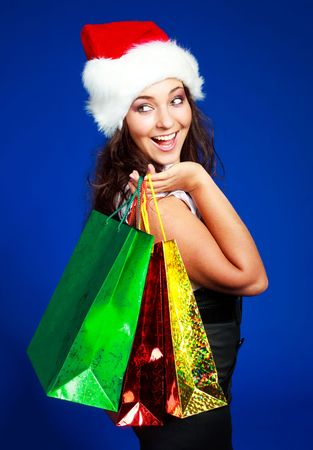 beautiful brunette girl wearing a Santas hat with a lot of shopping bags   photo