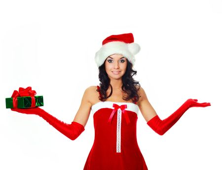 beautiful young brunette woman dressed as Santa with a present in her right hand and her left hand free, place your product here photo