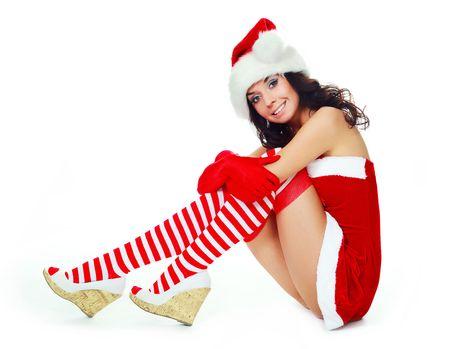 beautiful dreamy girl dressed as Santa sitting on the floor photo