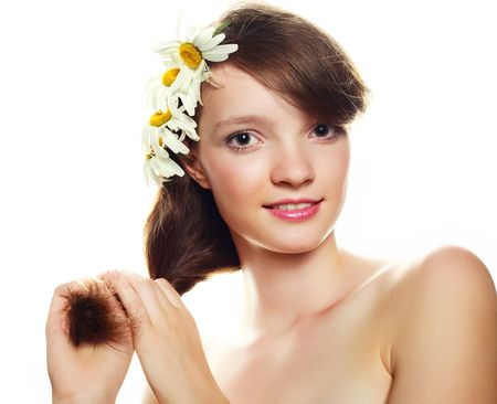 pretty girl with many camomile flowers against white background photo