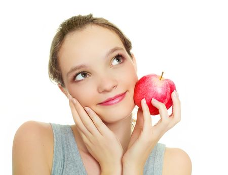 beautiful dreamy young woman with an apple isolated against white background photo