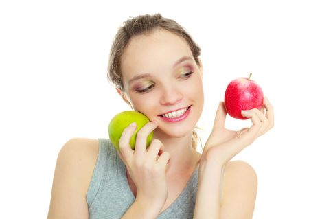 beautiful happy young woman with two apples looking at one of them isolated against white background photo
