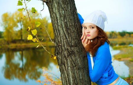 pretty depressed girl standing near the tree in the autumn park photo