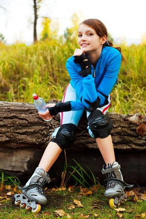 rollerskates: pretty happy girl with rollerskates drinking water in the park