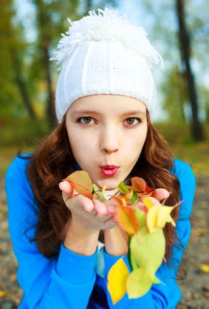 outsides: beautiful happy girl blowing on the yellow leaves in her hands in the park