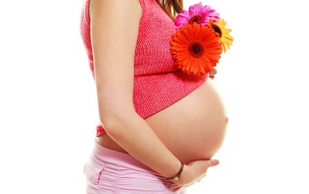belly of a young pregnant caucasian woman holding flowers in her hand