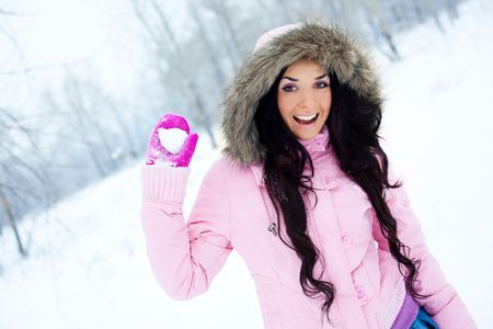 pretty young brunette woman throwing a snowball outdoor in a winter park photo