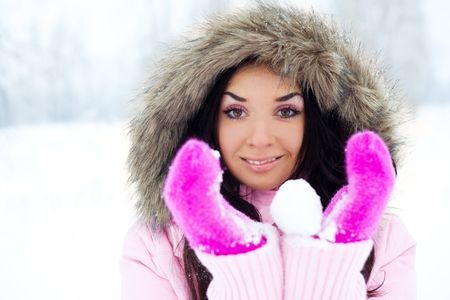 pretty young brunette woman with a snowball outdoor in a winter park photo