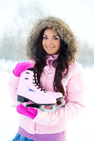 beautiful young brunette woman wearing warm winter clothes going to ice skating Stock Photo - 5986714