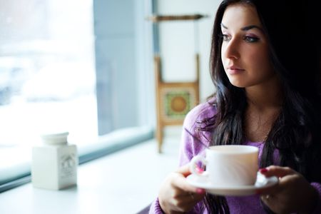 hesitations: pretty young woman sitting by the table with a cup of tea Stock Photo