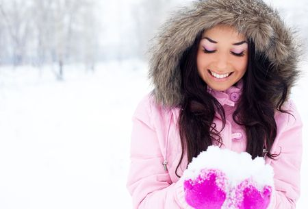 pretty young brunette woman holding snow outdoor in a winter park photo