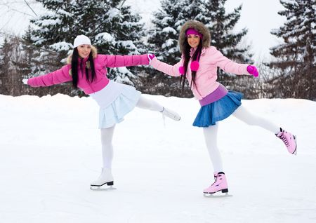 rink: two beautiful girls wearing warm winter clothes ice skating