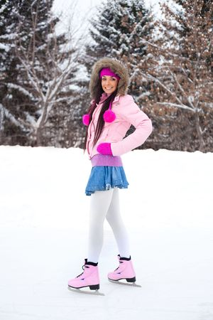 happy beautiful girl wearing warm winter clothes ice skating Stock Photo - 6027465