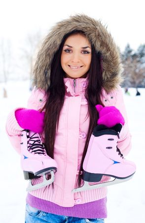 beautiful brunette girl wearing warm winter clothes going to ice skate Stock Photo - 6027460