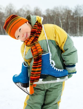 iceskating: cute little boy wearing warm winter clothes going ice skating  Stock Photo